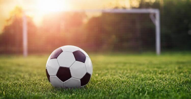 Image d'un ballon de football sur l'herbe près de poteaux de but.