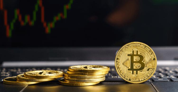Des Bitcoins sur un ordinateur portable avec un graphique de trading à l'écran
