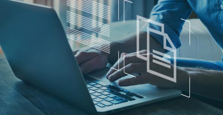 Une personne tapant sur un ordinateur portable avec du texte et des graphiques de documents