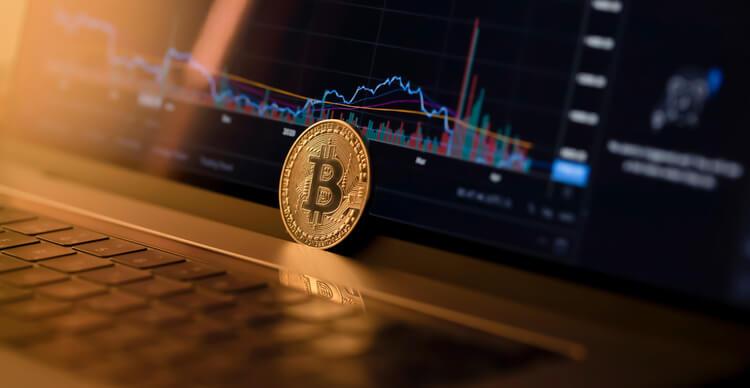 Image d'un Bitcoin sur un ordinateur portable avec un graphique de trading